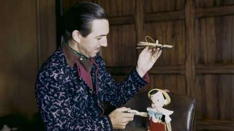 Walt Disney examines a Pinocchio marionette circa 1939.