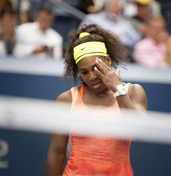 Serena Williams reacts after hitting a losing a