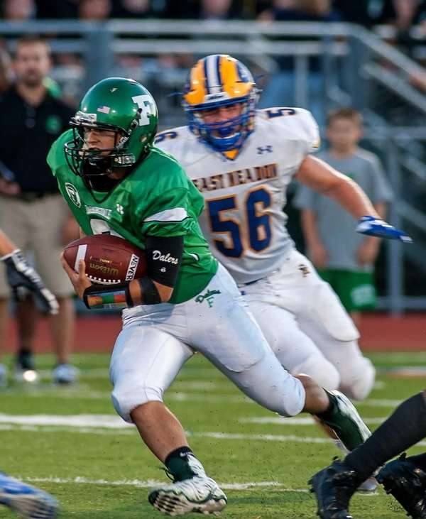 East Meadow's Kyle Barker, right, chases Farmingdale's Anthony