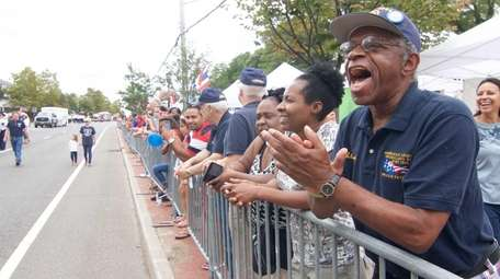 Alexander Samuels, right, joins others in cheering on