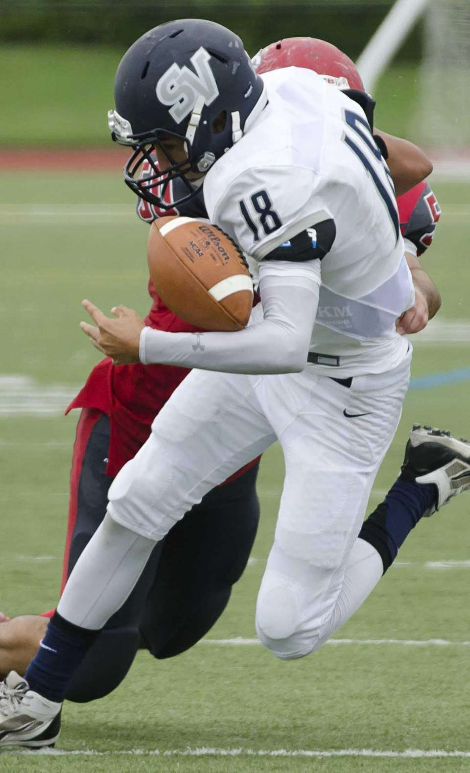 St. Joseph by-the-Sea's Francis Perry, front, gets hit