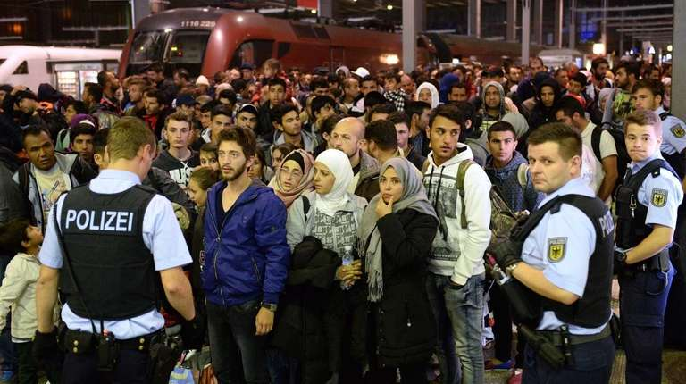 Refugees gather together after arriving from Budapest, Hungary,