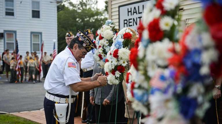 John Menechino places a wreath during the Patriot