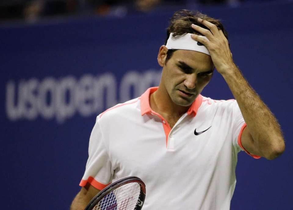 Roger Federer, of Switzerland, adjusts his headband between