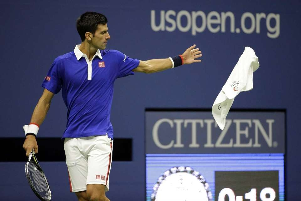 Novak Djokovic, of Serbia, tosses a towel back