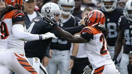 Oakland Raiders quarterback Derek Carr (4) stiff arms