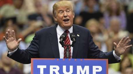 Donald Trump talks during a large rally inside