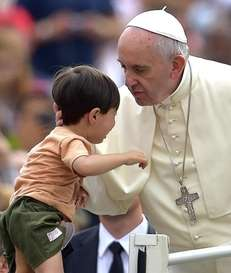 Pope Francis blesses a child as arrives in