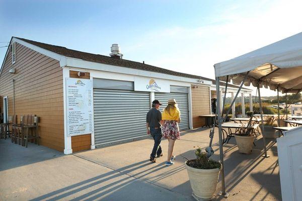 A couple walks past the Cedar Beach Bar