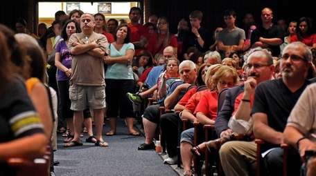 Concerned audience members listen as possible school cuts