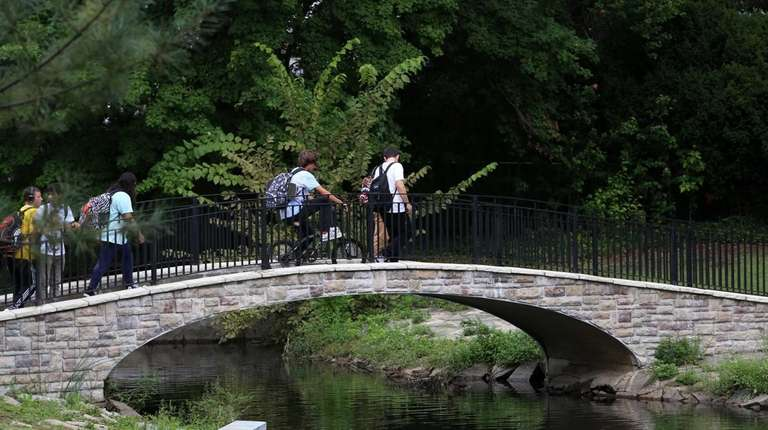 Teenagers walk home from school through Hall's Pond