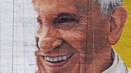 A man paints a mural of Pope Francis