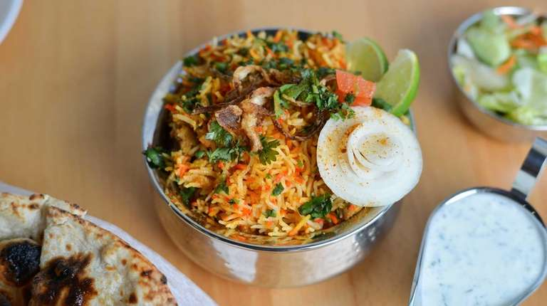 Chicken biryani garnished with fried onion and lime