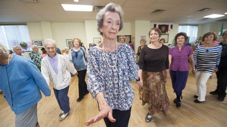 Betty Yoelson, center, celebrates her 100th birthday dancing