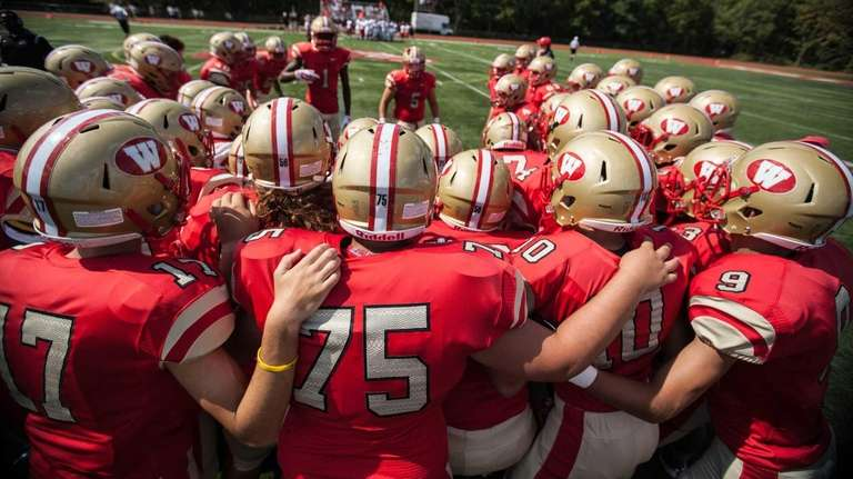 Half Hollow Hills West players huddle before a