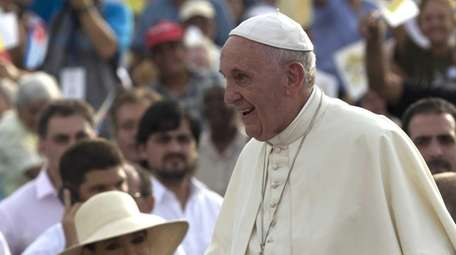 Pope Francis rides his popemobile past Cuba President