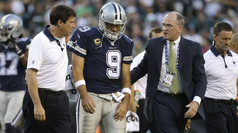 Dallas Cowboys' Tony Romo is helped off the
