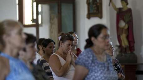 A woman prays as she attends Mass at