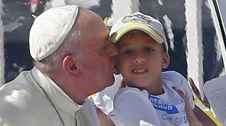 Pope Francis kisses a boy as he arrives