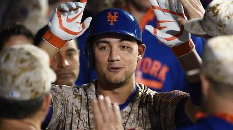 New York Mets leftfielder Michael Conforto is greeted