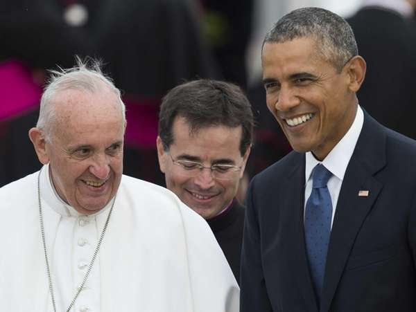 Pope Francis waves alongside President Barack Obama upon