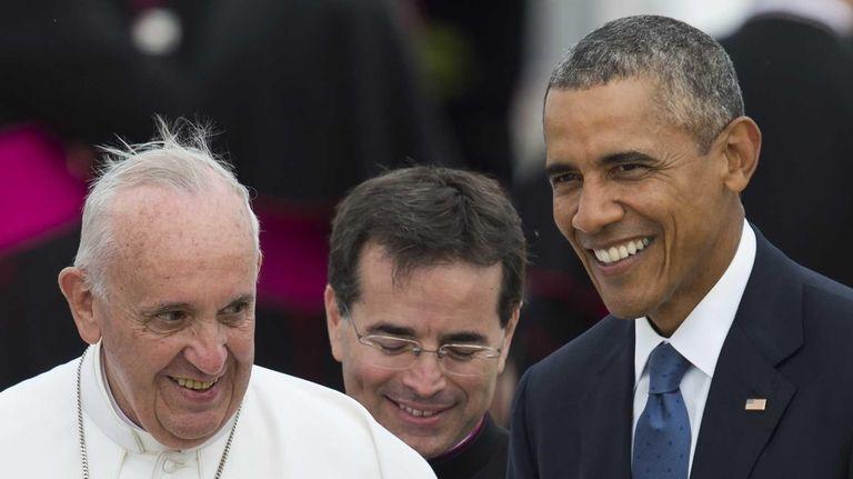 Pope Francis waves alongside President Barack Obama upon