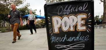 A sign advertises Pope Francis merchandise in downtown