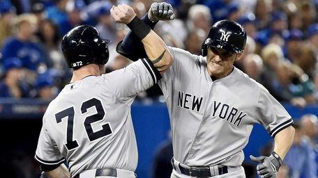 The New York Yankees' Greg Bird, right, celebrates