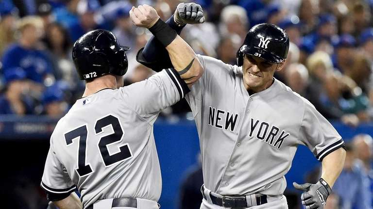 The New York Yankees' Greg Bird, right, celebrates