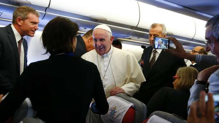 Pope Francis greets journalists on his flight from