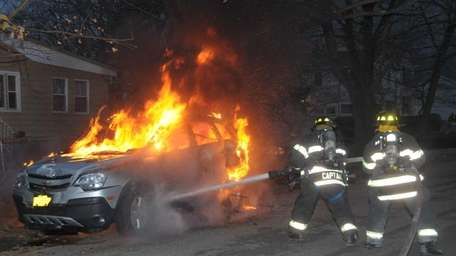 Firefighters douse a Chevrolet Captiva engulfed in flames