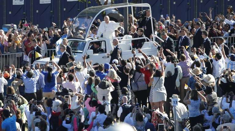 Pope Francis waves from the popemobile as he