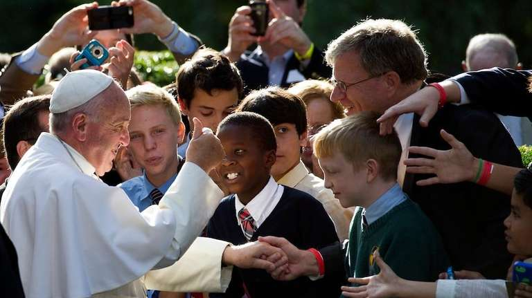 Pope Francis gives a thumbs-up while greeting school