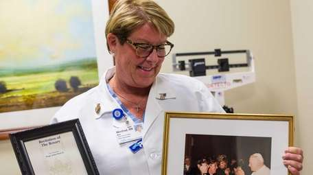 Winnie Mele, 57, a nurse, holds a photo