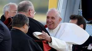 Pope Francis is greeted by Cardinal Timothy Dolan