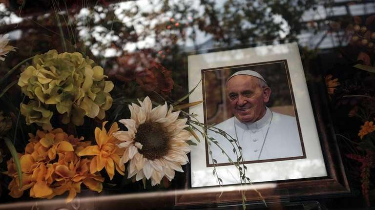 A portrait of Pope Francis sits in a