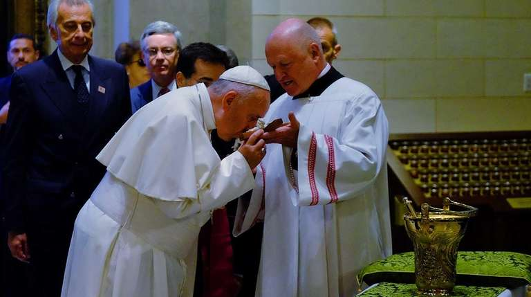 Pope Francis kisses the cross at the entrance