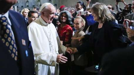 Pope Francis greets attendees as he leaves an