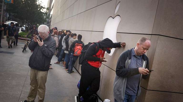 Customers wait in line at the apple store