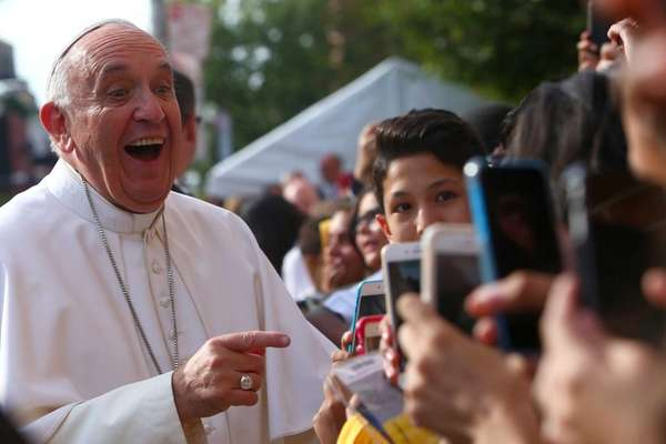 Pope Francis smiles at shutterbug students during a