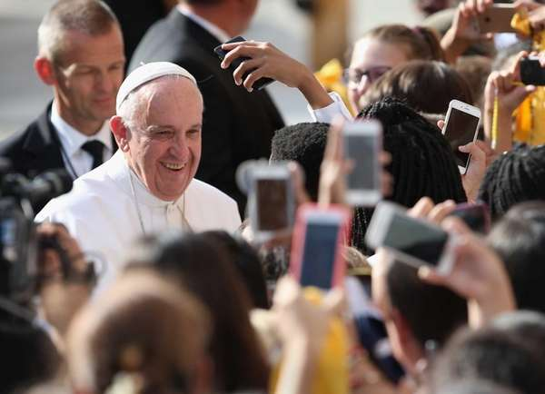 School children photograph Pope Francis after his arrival