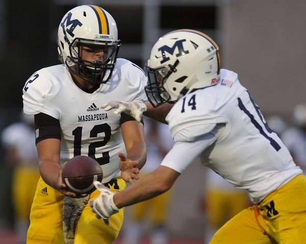 Massapequa quarterback Brad Baldinger, left, hands off to