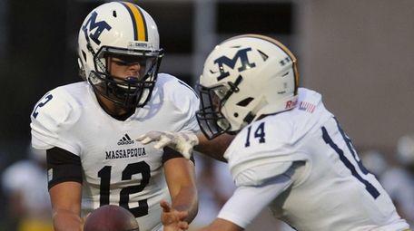 Massapequa quarterback Brad Baldinger, left, hands off to
