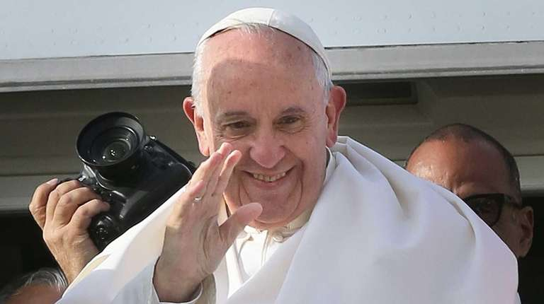 Pope Francis waves to the hundreds of faithful