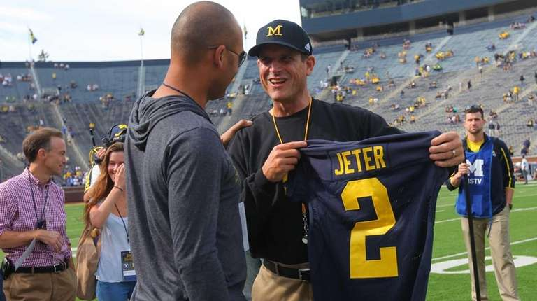 Head coach Jim Harbaugh, right, of the Michigan