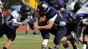 Smithtown West's James Caddigan (28) crashes into the