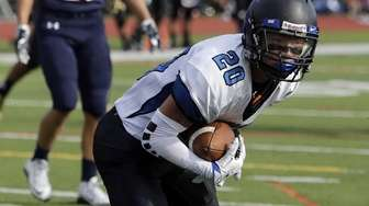 Centereach's Rob Montgomery (20) cradles the football on