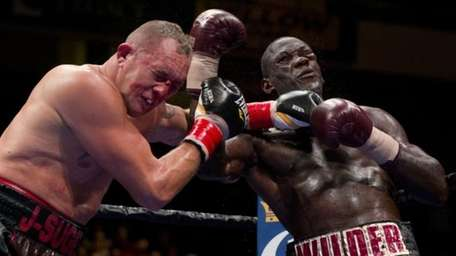 Heavyweight boxing champion Deontay Wilder, right, punches Johann
