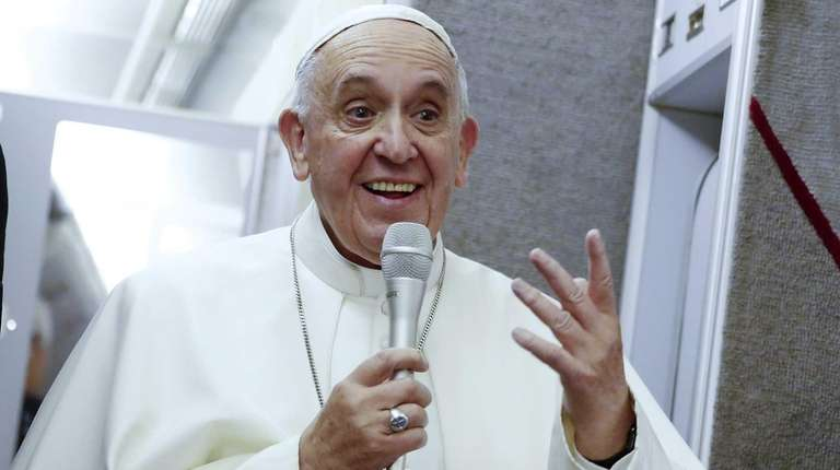 Pope Francis speaks during the flight back to