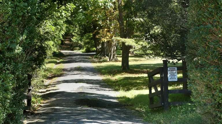 A tree-lined driveway leads into the property on